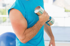 Mid section of a sporty man with dumbbell in gym Royalty Free Stock Photo