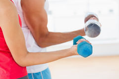 Mid section of a sporty young couple with dumbbells Royalty Free Stock Photos
