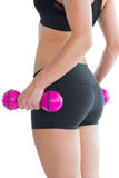 Mid section of sporty young woman holding pink dumbbells Stock Images