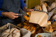 Mid section of staff packing croissant in paper bag at counter Stock Photography