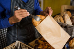 Mid section of staff packing croissant in paper bag at counter Stock Photo