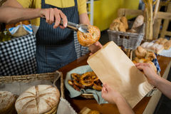 Mid section of staff packing croissant in paper bag at counter Stock Images