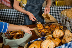 Mid section of staff packing sweet food in paper bag at counter Stock Images