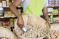 Mid section of store clerk with basket of peanuts Royalty Free Stock Photo