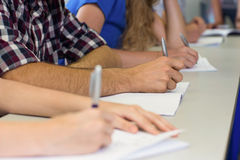 Mid section of students writing notes in classroom Stock Photo