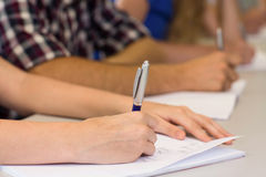 Mid section of students writing notes in classroom Stock Images