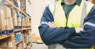 Mid section of supervisor standing with arms crossed. In warehouse Stock Photos