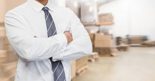 Mid section of supervisor standing with arms crossed. In warehouse Stock Images