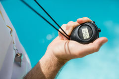 Mid section of swim coach holding stopwatch near poolside Stock Photography