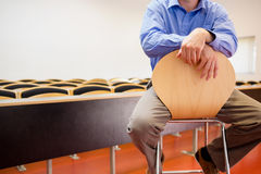 Mid section of a teacher on chair in lecture hall. Mid section of a male teacher sitting on chair in the lecture hall Royalty Free Stock Photography
