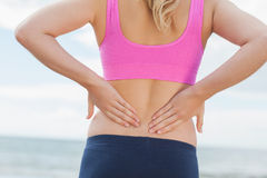 Mid section of toned woman from back pain on beach Stock Images