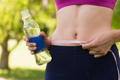 Mid section of a toned woman measuring waist in park Stock Image