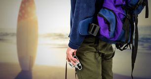 Mid section of tourist with camera and surfboard on beach Stock Photos