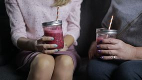 Mid section of women with smoothie jars talking. Mid section of two women with fresh berry smoothies chatting and gesturing while sitting on the couch at home stock footage