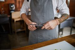 Chef Sharpening Knife. Mid section of unrecognizable chef sharpening knife in kitchen, copy space stock image