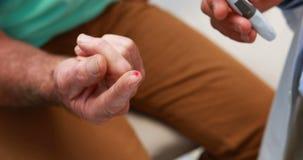 Mid-section van arts die hogere geduldige bloedsuiker onderzoeken stock videobeelden
