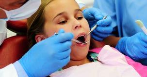 Mid-section van tandarts en verpleegster die een jonge patiënt met hulpmiddelen onderzoeken stock videobeelden
