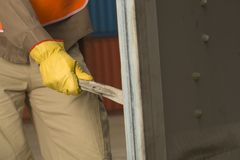 Mid section view of a dock worker opening a cargo container Royalty Free Stock Images