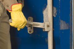 Mid section view of a dock worker opening a cargo container Stock Images