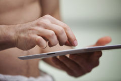 Mid section view of a man using a digital tablet Stock Images