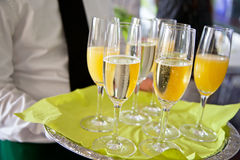 Mid section view of waiter serving champagne and orange juice on Royalty Free Stock Image