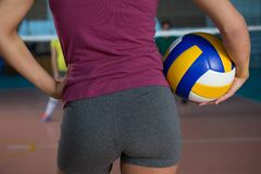 Mid section of volleyball player holding ball. While standing at court Stock Photos