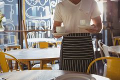 Mid section of waiter holding coffee cups Royalty Free Stock Image