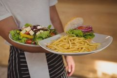 Mid section of waiter holding plates with French fries and salad. In cafe Stock Image