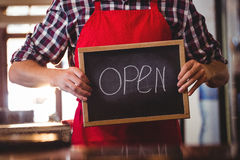 Mid section of waiter showing chalkboard with open sign Stock Photo