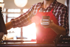 Mid section of waiter showing credit card machine. At cafe Stock Images
