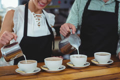 Mid section of waiter and waitress making cup of coffee at counter Stock Photo