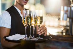 Mid section of waitress holding serving tray with champagne flutes Royalty Free Stock Images