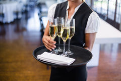 Mid section of waitress holding serving tray with champagne flutes  Stock Image