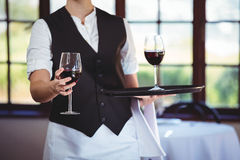Mid section of waitress offering a glass of red wine Royalty Free Stock Image