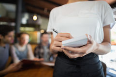 Mid section of waitress writing orders of customers. In restaurant Royalty Free Stock Photography
