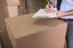 Mid section of warehouse worker with clipboard Stock Images