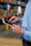 Mid section of warehouse worker using digital tablet Stock Image