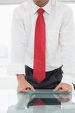 Mid section of a well dressed businessman with clenched fists on desk Royalty Free Stock Image