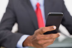 Mid section of well dressed businessman text messaging Royalty Free Stock Photo