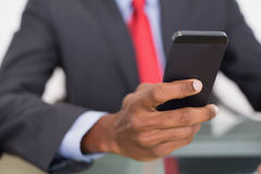 Mid section of well dressed businessman text messaging Stock Images