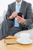 Mid section of a well dressed man text messaging at home Stock Images