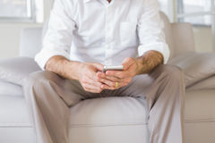 Mid section of a well dressed man text messaging at home Stock Photos
