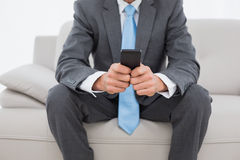 Mid section of a well dressed man text messaging on sofa Royalty Free Stock Photo