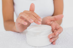 Mid section of woman applying cream Stock Photo