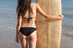 Mid section of a woman in bikini bottom with surfboard on beach Stock Images
