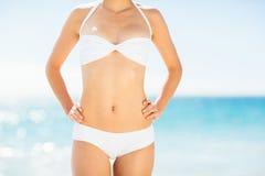 Mid section of woman in bikini standing on beach. Mid section of woman in white bikini posing on beach Stock Photo
