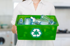 Mid section of woman carrying box with recycling symbol Stock Photos