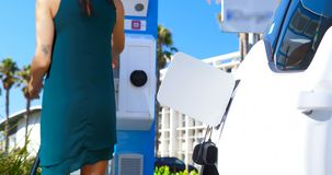 Woman charging electric car at charging station 4k