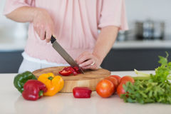Mid section of woman chopping vegetables. At counter in kitchen Stock Image