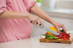 Mid section of a woman chopping vegetables in kitchen Stock Photography